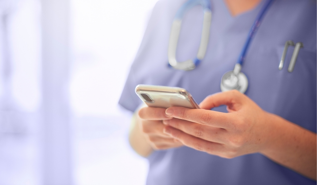 A healthcare practitioner holding a mobile phone