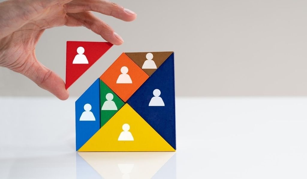 An image of a hand placing a building block on top of others with an icon of a person on each block.